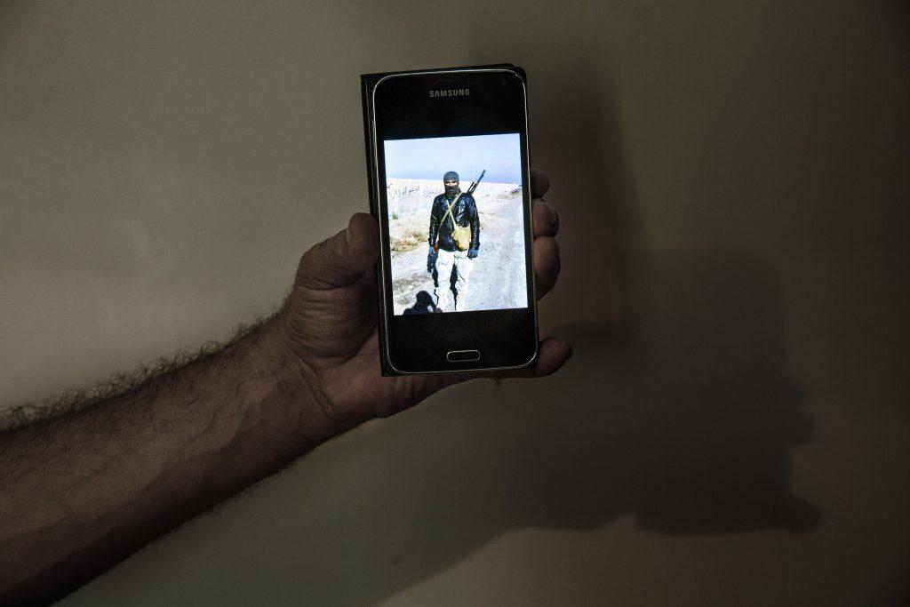 Europa, Turchia, Hatay. Abu Hassan, 40 anni, combattente ribelle del fronte di Jabhat Al Asala, mostra una sua foto sul telefonino dove è vestito in abiti da combattimento nella sua stanza all'hotel Alice di Reyhanli nella provincia Hatay. Foto di Marco Gualazzini