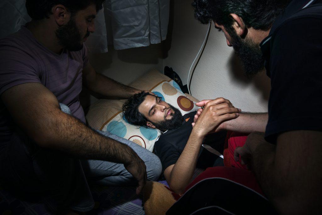 Europa, Turchia, Hatay. Un combattente ferito alla testa ancora in stata di incoscienza viene accudito dagli altri ospiti della casa. È accolto in un luogo sicuro a Reyhanli nella provincia Hatay con altri ribelli feriti. Foto di Marco Gualazzini