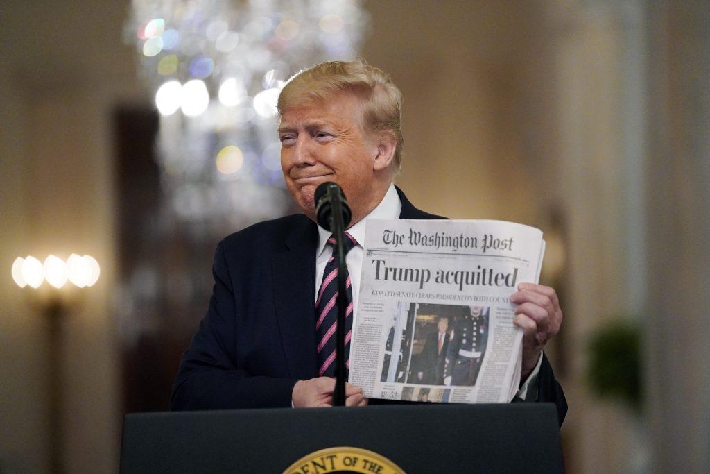 Il presidente Donald Trump mostra il titolo del Washington Post, giornale molto critico nei suoi confronti, sul risultato dell'impeachment (LaPresse)