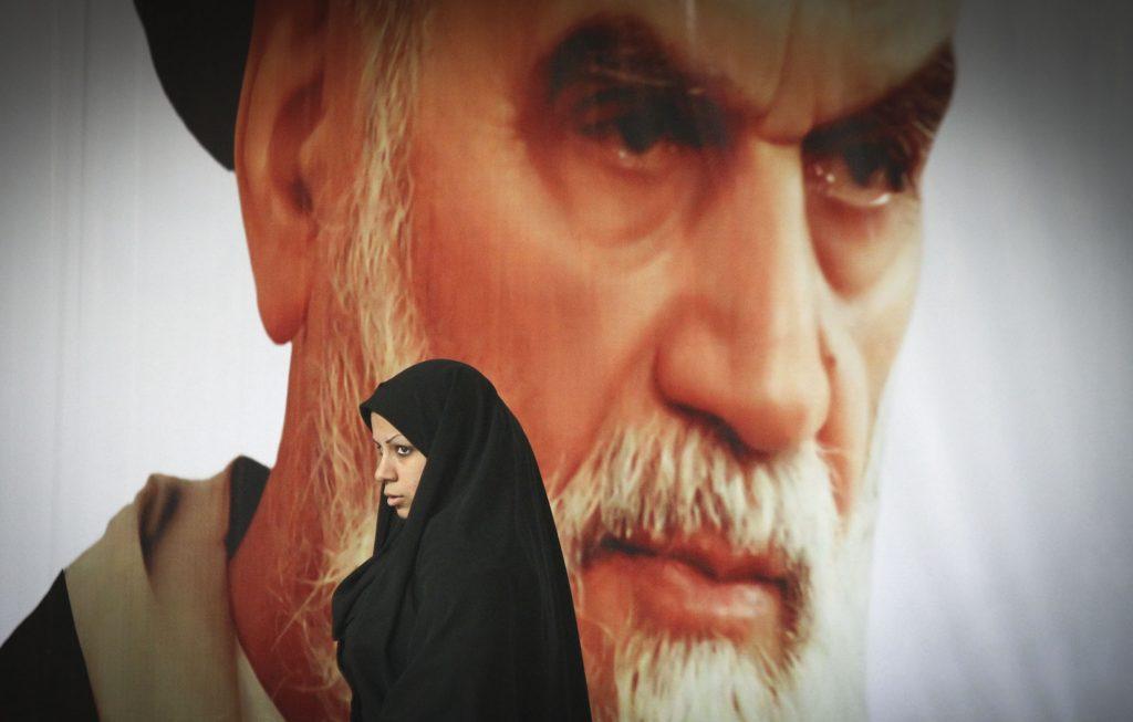 Una donna cammina davanti al volto dell'ayatollah Ruhollah Khomeini (LaPresse)