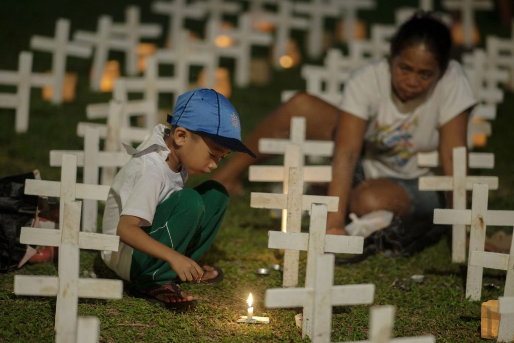 In this photo taken on November 8, 2018, a boy and his mother light candles next to crosses to commemorate the fifth anniversary of Super Typhoon Haiyan in Tacloban City, Leyte province, central Philippines