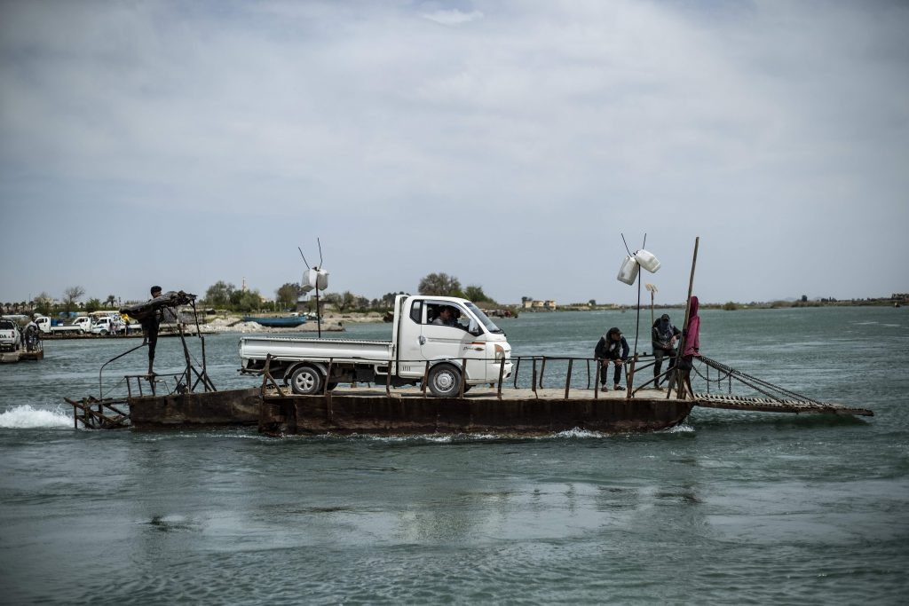 A vehicle is transported on a platform on the Euphrates river in the northern Syrian city of Raqa, the former Syrian capital of the Islamic State Delil Souleiman/AFP)