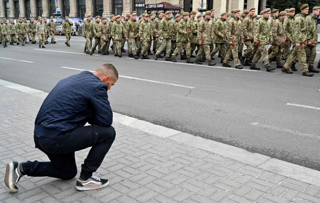 A man kneels before servicemen who take part in a march marking Remembrance and Reconciliation Day in Kiev on May 8, 2019. (Photo by Sergei Supinsky/AFP)