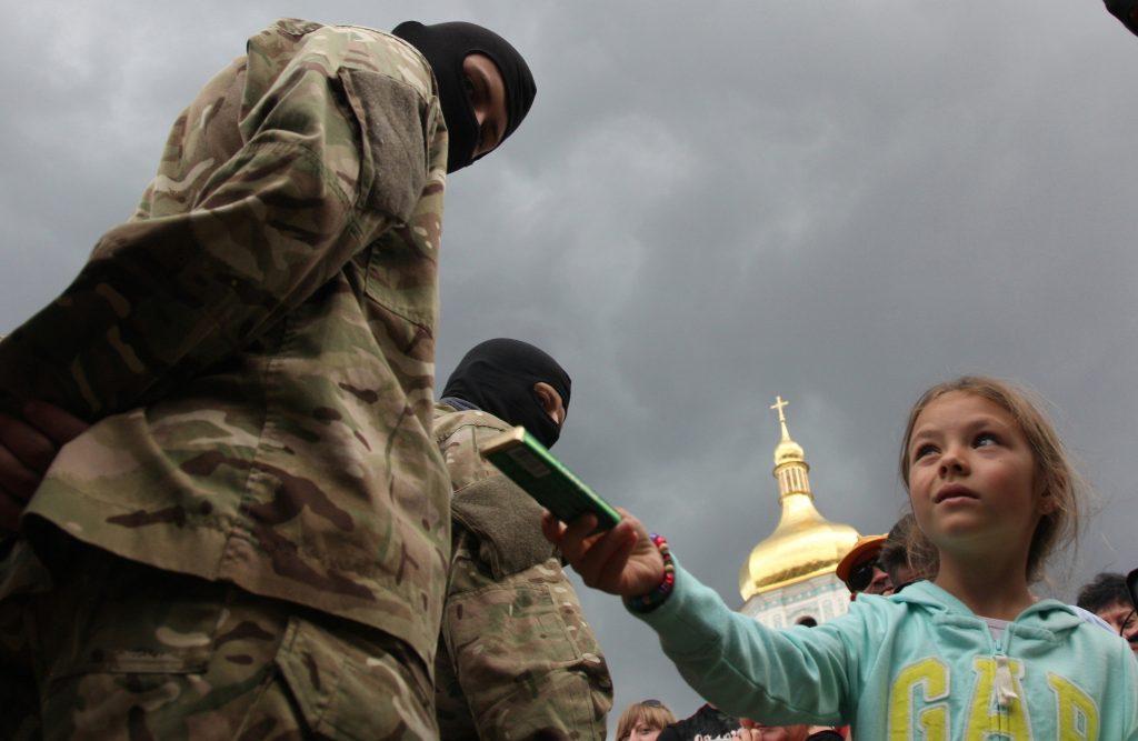 Una bambina con un volontario del battaglione Azov (LaPresse)