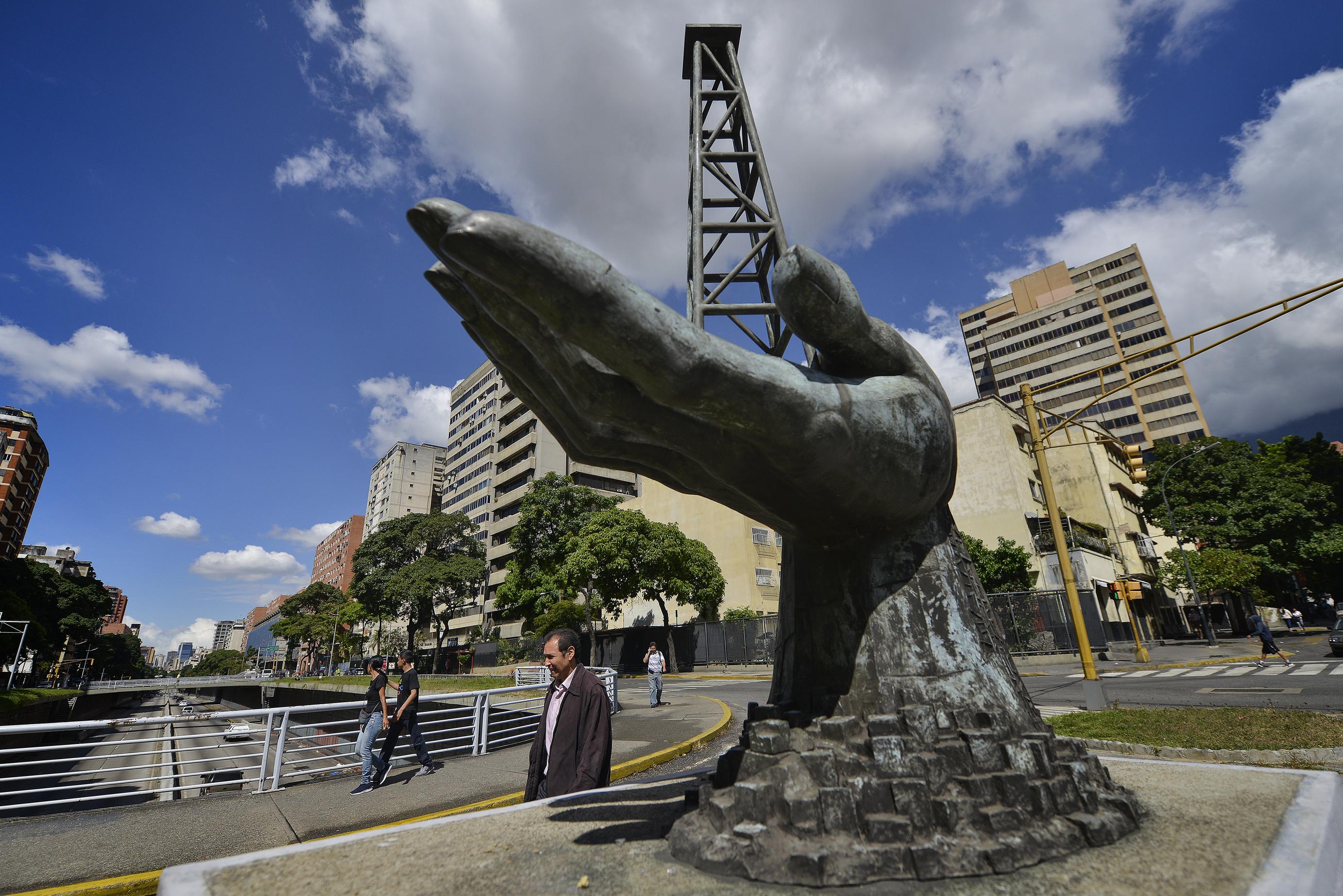 Una scultura di una mano che regge una struttura di pozzi petroliferi fuori dalla compagnia petrolifera statale venezuelana Pdvsa a Caracas (LaPresse)