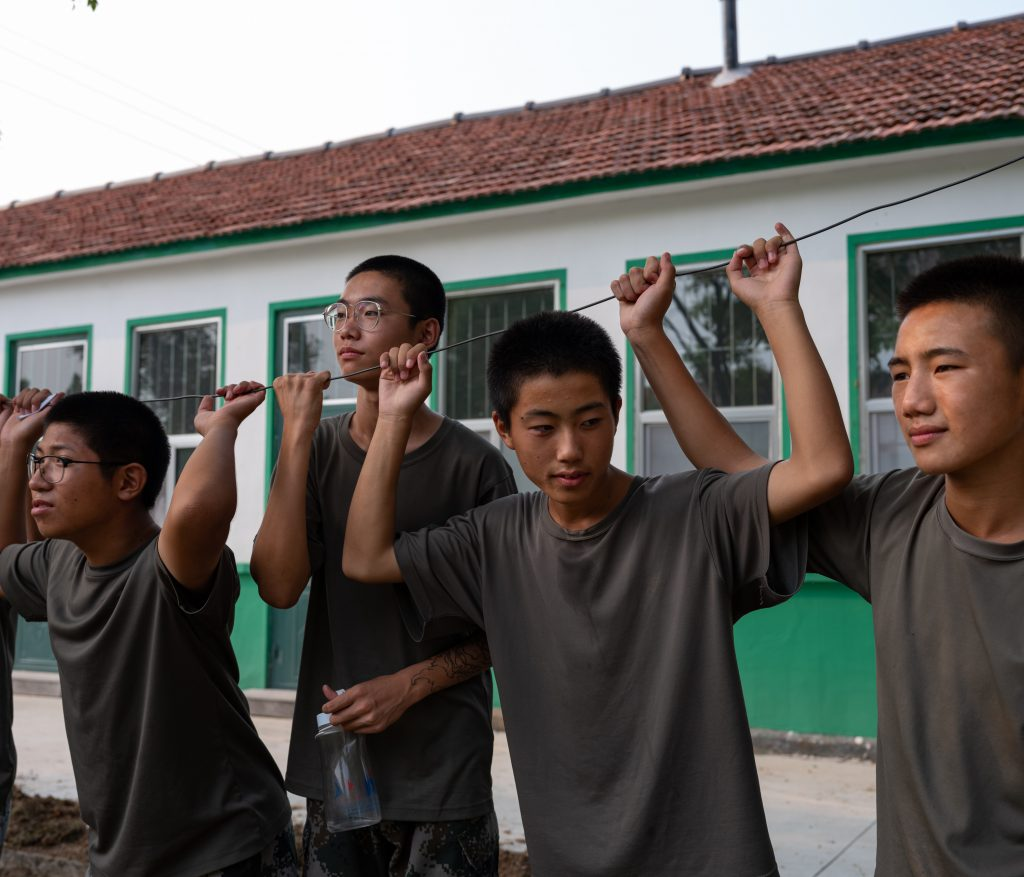 Guys rest and wait their turn in some physical exercises in the garden of the recovery camp from internet and videogaming addiction in Weifang