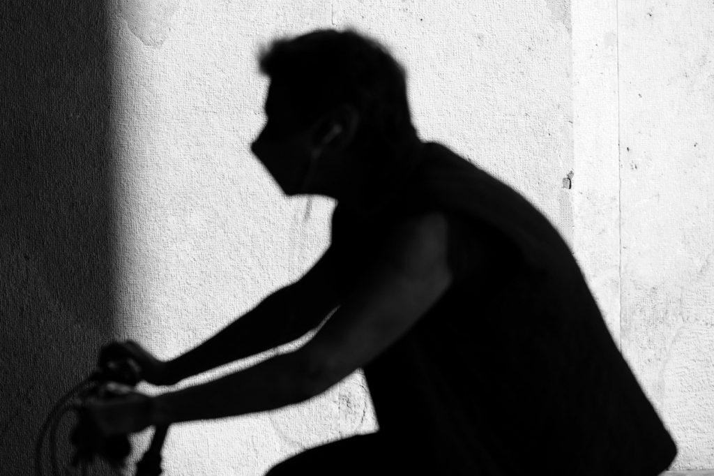 Un ragazzo indossa una mascherina mentre gira in bicicletta le vie di Milano, foto di Vittorio Zunino Celotto per Getty