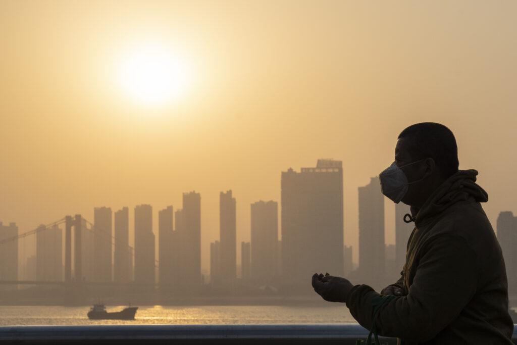 Un uomo indossa una maschera il sole tramonta lungo la riva del fiume a Wuhan (LaPresse)